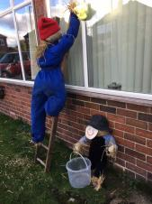 Scarecrows cleaning windows